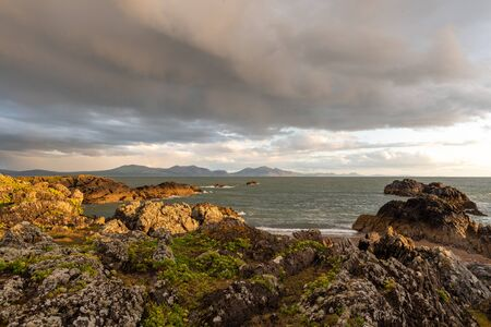 View of the llyn peninsula from Ynys Llanddwyn on Anglesey, North Wales at sunset. 스톡 콘텐츠 - 132786715