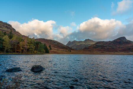 Beautiful and moody morning fall light at Blea Tarn in the English Lake District with views of the Langdale Pikes, and Side Pike during autumn. 스톡 콘텐츠 - 133052267