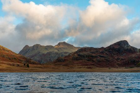 Beautiful and moody morning fall light at Blea Tarn in the English Lake District with views of the Langdale Pikes, and Side Pike during autumn. 스톡 콘텐츠 - 133051749