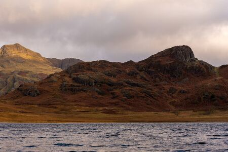 Beautiful and moody morning fall light at Blea Tarn in the English Lake District with views of the Langdale Pikes, and Side Pike during autumn. 스톡 콘텐츠 - 133051489