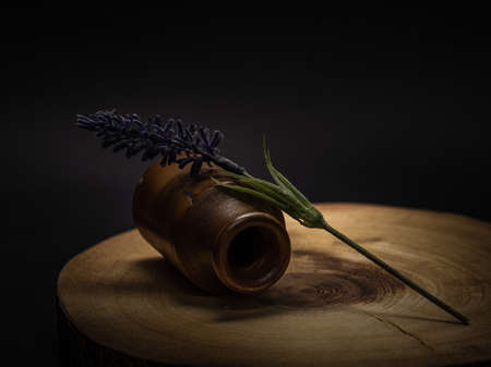 A single faux lavender stem and old bottle against a wood, and black background.