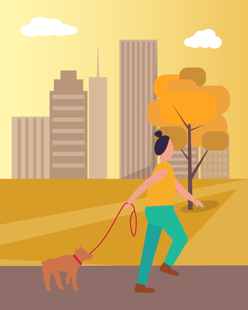 Girl in the process of walking her dog in autumn city park.