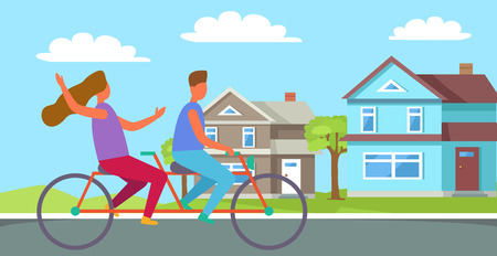Couple riding on tandem or twin bicycle on background of cottage houses. Happy family spend time together in rural countryside