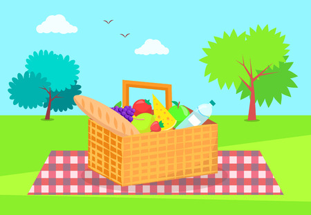 Picnic basket fresh vegetables and fruits, long loaf of french bread, piece of cheese, mineral water on checkered blanket on background of green trees