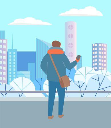 Uomo che cammina da solo attraverso il parco invernale urbano. Persona in vestiti caldi, cappello e sciarpa in piedi con il telefono in mano. Bellissimo paesaggio innevato della città sullo sfondo. Illustrazione vettoriale in stile piatto