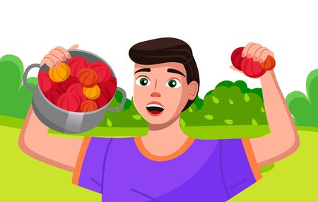 Happy young farmer holding a pan with bright fresh vegetables. Gardener is proud of his harvest. Farm worker on the summer country landscape is telling about plant, green growing, useful agriculture