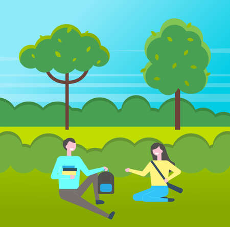 Young students with books sitting at grass in park. Couple of girl and guy studying outdoors at nature. Spend time together. Girl with bag smiling to guy with backpack. Green trees at background