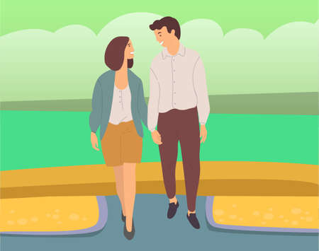 Couple walking down the street. Young guy and girl holding hands, looking at each other, walking in summer day in city park, romantic walk. Pleasant promenade in open air on a date, active lifestyle