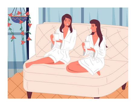 Two young beautiful smiling women are sitting with bent legs on a large bright comfortable sofa with cups of tea or drink, white bathrobes. Girls in the spa. Beauty treatments and relaxation