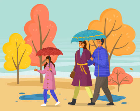 Parents and daughter spend time together on a rainy october day go down the street past yellow trees. Family walking in the rain with umbrella and wearing raincoats in the city park in autumn season.