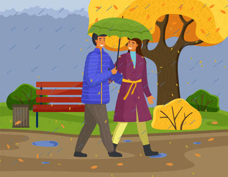 Married couple walks in autumn park or forest. Girl in violet raincoat, guy wears blue jacket carries green umbrella. Fall landscape, rain, wind weather. Yellow landscape. Spend time together