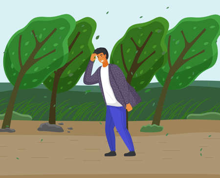 Guy in jeans and shirt overcomes strong gusts of wind, protecting face with hand. Green trees are sloping from the wind, storm. Countryside, country road, summer or spring time. Storm before the rain