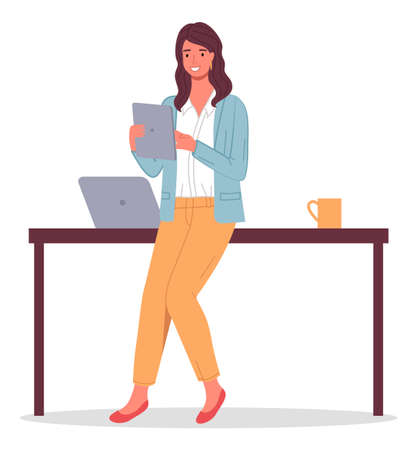 Businesswoman holding digital tablet in hands. Business lady leaning on table with laptop, cup. Confident smiling happy woman brunette wearing pants, blouse, cardigan. Office worker portrait