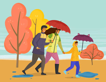 Family walking in the rain with umbrella and wearing raincoats in the city park in autumn season. Parents and daughter spend time together on a rainy october day run down the street past yellow trees