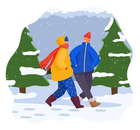 Winter, couple of happy girl and guy wearing warm clothes jacket and hat, young adult people walking in forest among snow-covered fir-trees, outdoors activity, happy smiling in love man and woman