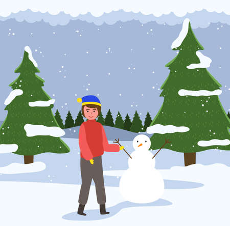 A male child walks in the forest and playing with the snow. Happy boy in warm clothes is standing against the background of a snowy christmas tree. Male character is sculpting a snowman outside