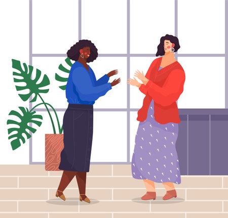 Two women standing and talking in office. Dark-skinned girl wears jewelry, blue blouse, denim skirt, white-skinned girl wears sweater, patterned dress. Women laugh and gesticulate in modern office
