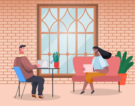 Business people man and woman are sitting at the table typing on laptops and talking in modern interior with brick wall. Office workers discussing matters. Business meeting and consideration