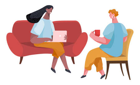Businesswomen dressed in formal clothes are sitting on the sofa together, talking, drinking coffee. Office workers discussing matters. Friendly colleagues or friends communicating during the break