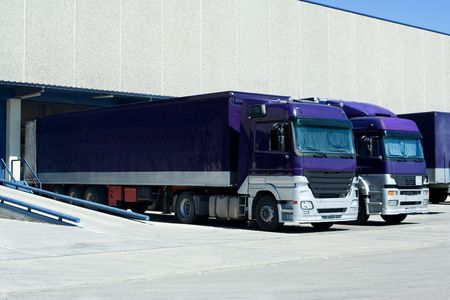 truckload: Purple Trucks Loading Goods at the Dock Stock Photo
