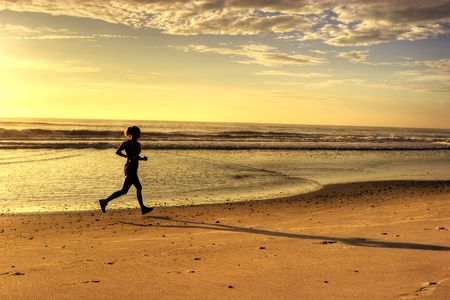 Woman Running on the Beach in the Morning Banque d'images
