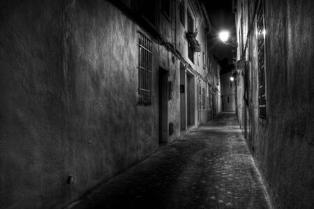 spook: A Narrow European Street at Night in Black and White