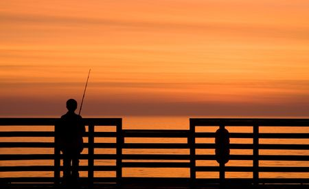 Boy fishing off a pier during sunrise Stock Photo - 6931506