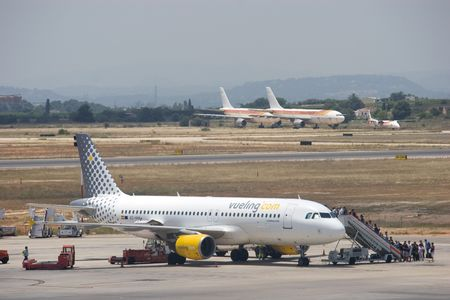 expects: VALENCIA, SPAIN - JUNE 24: Vueling Airlines will start connecting passengers through its base at Barcelona from July 5, a move that it expects will allow it to carry 250,000-350,000 more travelers . A Vueling aircraft at the Valencia Airport on June 24, 2