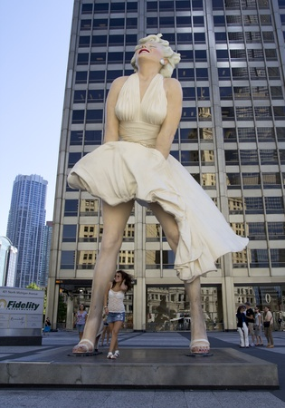 CHICAGO - AUGUST: An unknown tourist poses in front of a giant 26 foot tall sculpture of Marilyn Monroe in Chicago on August 25, 2011. Created by artist Seward Johnson, the work stands in a square on Michigan Avenue.