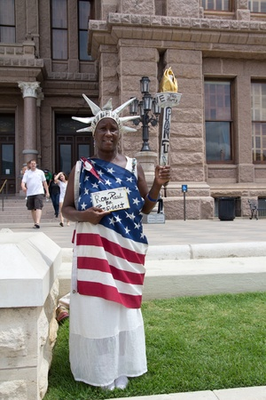 ron: AUSTIN, TX - AUG 13: An unidentified Ron Paul Supporter demonstrates in front of the Texas State Capitol Building in Austin, Texas on August 13, 2011.  Ron Paul is a 2012 Republican Presidential candidate.