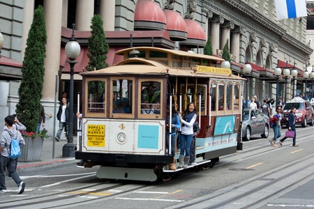 frisco: SAN FRANCISCO - AUG 20: Passengers enjoy a ride in a cable car on August 20, 2011 in San Francisco. It is the oldest mechanical public transport in San Francisco which is in service since 1873.