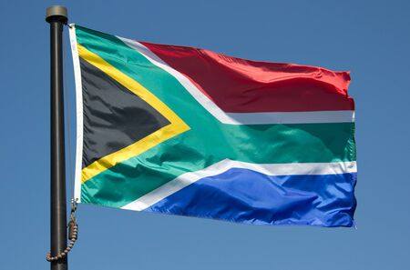 The South African Flag blowing in the wind with blue sky Фото со стока