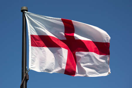 flaunt: St George Flag blowing in the wind with blue background