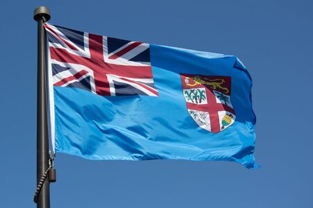 Fiji Flag blowing in the wind with blue sky photo