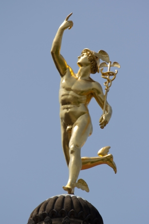 STUTTGART, GERMANY - JUNE 30: The gilt statue of the Roman God Mercury made by the German sculptor Johann Ludwig von Hofer in 1862, on top of the Old Chancellary Building on June 30, 2012 in Stuttgart, Germany.
