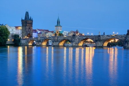 PRAGUE, CZECH REPUBLIC - AUGUST 4: Tourists crossing the Charles Bridge in early evening on August 4, 2012 in Prague, Czech Republic.  Its construction started in 1357 under the auspices of King Charles IV.