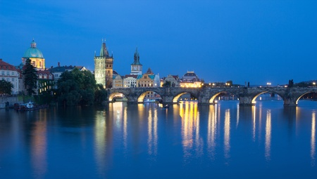 auspices: PRAGUE, CZECH REPUBLIC - AUGUST 5: Tourists crossing the Charles Bridge in early evening on August 5, 2012 in Prague, Czech Republic.  Its construction started in 1357 under the auspices of King Charles IV.