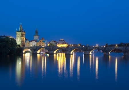 PRAGUE, CZECH REPUBLIC - AUGUST 5: Tourists crossing the Charles Bridge in early evening on August 5, 2012 in Prague, Czech Republic.  Its construction started in 1357 under the auspices of King Charles IV.