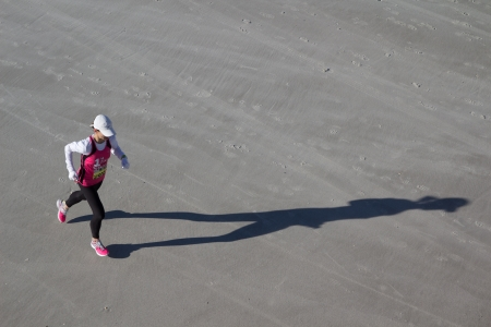 JACKSONVILLE, FLORIDA - FEBRUARY 17: A female runner on the beach leg of the 6th Annual 26.2 with Donna Marathon on February 17, 2013 in Jacksonville, Florida.