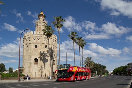 SEVILLE, SPAIN - MAY 16: A City Sightseeing tour bus at the Torre de Oro on May 16, 2013 in Seville, Spain. City Sightseeing operates in 100 cities worldwide and carries about eight million passengers per year.