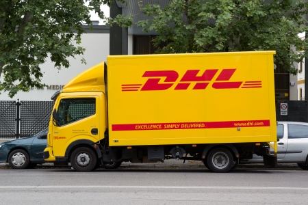 delivery service: SEVILLE, SPAIN - MAY 15: A DHL delivery truck on the street in Seville, Spain on May 15, 2013. DHL is a world wide courier company that operates in 220 countries with over 285,000 employees.