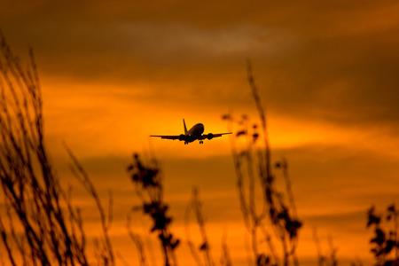 空港に近づく航空機のシルエット。 写真素材