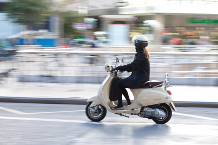 VALENCIA, SPAIN - JANUARY 27, 2014: A woman on a Vespa scooter traveling in the town center of Valencia with motion blur. Vespa is an Italian brand of scooter manufactured by Piaggio. The name means wasp in Italian.