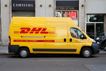 delivery service: VALENCIA, SPAIN - JANUARY 28, 2014: A DHL delivery van on the street in the city center of Valencia. DHL is a world wide courier company that operates in 220 countries with over 285,000 employees.