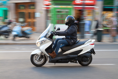 VALENCIA, SPAIN - JANUARY 28, 2014: A Woman commuter on a scooter in the city center of Valencia. Due to the economic crisis, scooter sales in Europe have declined 20 percent in the year 2013. Editorial