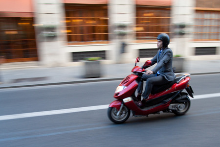 VALENCIA, SPAIN - JANUARY 28, 2014: A businessman on a scooter in the city center of Valencia. Due to the economic crisis, scooter sales in Europe have declined 20 percent in the year 2013.