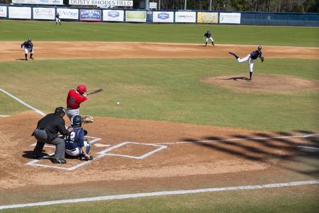 JACKSONVILLE, FL-22 février 2014: Un joueur de l'Université Fairfield (en rouge) frappe le baseball lors d'un match contre l'Université de North Florida à Jacksonville. Banque d'images - 26115456