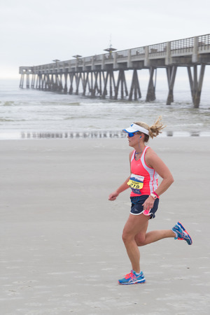 JACKSONVILLE, FL - FEBRUARY 23, 2014: Female runner, Kathleen Carey, on the beach leg of the 7th Annual 26.2 with Donna Marathon in Jacksonville, Florida.