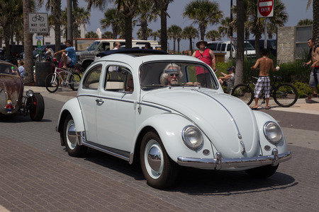 officially: JACKSONVILLE BEACH, FL - APRIL 27, 2014: A classic Volkswagen Beetle at the 68th annual Opening of the Beaches Parade in Jacksonville Beach, Florida. Each year the city holds a parade to officially open the beaches for the summer months.