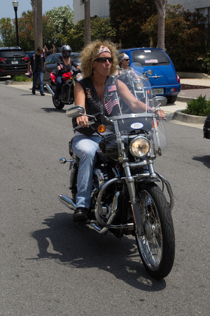 JACKSONVILLE BEACH, FL - APRIL 27, 2014: A woman biker (motorcycle) in the 68th annual Opening of the Beaches Parade. Each year the parade officially opens the beaches for the summer months.